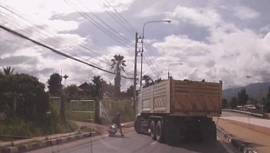 Đi mô tô chui gầm xe tải 20 tấn rồi lồm cồm bò ra