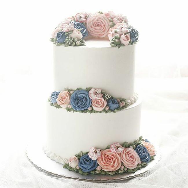 Lớp kem nền trắng tinh khôi nhấn nhá thêm vài bông hoa nhỏ xinh khiến chiếc bánh càng thêm thanh tao.