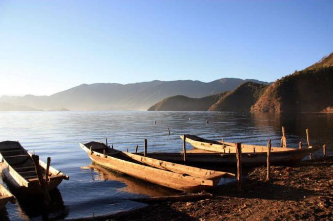 Những chiếc thuyền gỗ trên mặt nước rộng lớn của hồ Lugu, tạo nên khung cảnh rất yên bình và lãng mạn. Hồ nước này có diện tích 52 km, sâu 93m và nằm cách mặt nước biển 2.685 m.