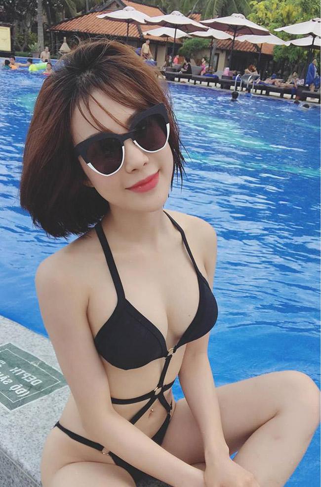 Nữ ca sĩ, người mẫu khoe thân hình đồng hồ cát trong bộ bikini màu đen bên cạnh bể bơi sang chảnh.