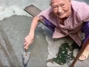 Xôn xao clip cụ bà ngoài 80 tuổi tự trộn xi-măng  vá  đường ở TP.HCM