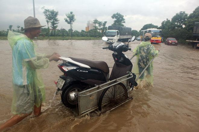 Đại lộ Thăng Long ngập sâu, dân xếp hàng thuê người chở xe - 8