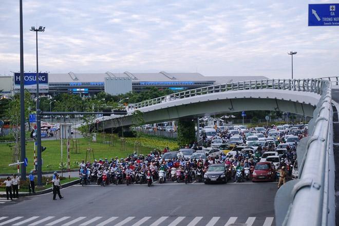 """Lực lượng chức năng phải """"trổ"""" thêm lối đi dưới gầm cầu vượtthép để các phương tiện di chuyển hướng ra từga quốc nội có thể di chuyển quađường Hồng Hà."""