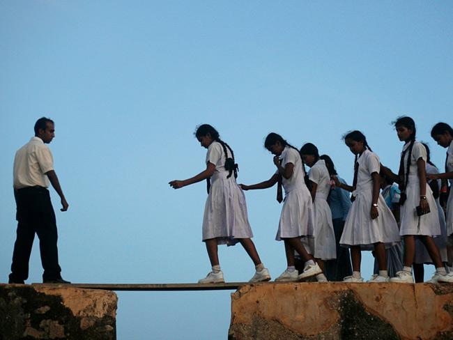 Những nữ sinh tại Sri Lanka phải vượt qua những tấm ván gỗ lỏng lẻo bắc qua pháo đài xây dựng từ thế kỷ 16 ở thị trấn ven biển Galle.
