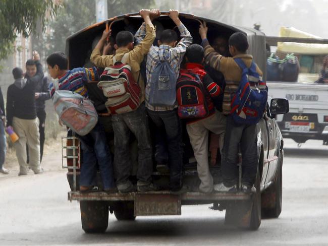 Học sinh Cairo, Ai Cập đi học bằng cách đu bám vào sau những chiếc xe tải đã chật cứng.