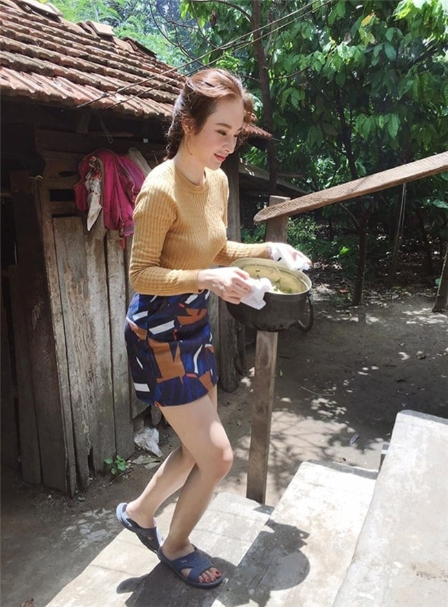 """Angela Phương Trinh trong một chuyến thăm vùng quê cũng lăn vào bếp như một cô thôn nữ. Bỏ đôi giày cao gót hàng hiệu,  """" bà mẹ nhí """"  mang một đôi dép cao su cho tiện đi lại."""