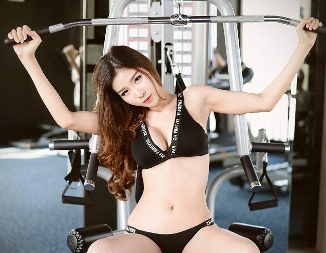 Cô thực hiện các bài tập với dụng cụ hỗ trợ trong phòng gym.