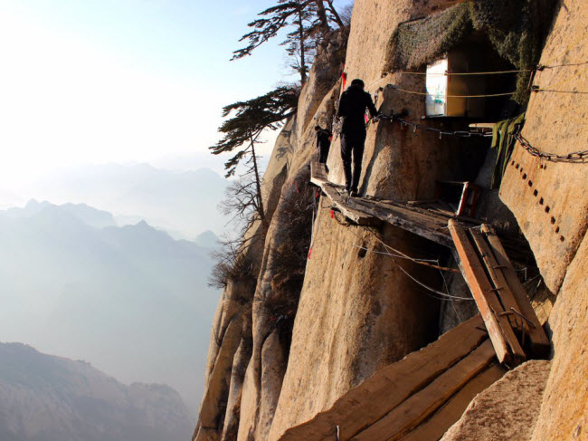 Núi Hóa Sơn, Trung Quốc: Lối đi dẫn tới đỉnh ngọn núi Hóa Sơn chỉ là những tấm gỗ mục trên vách đá dựng đứng cách & nbsp;mặt đất hàng trăm mét. Được coi là tuyến đi bộ nguy hiểm nhất thế giới, khoảng 100 người đã tử vong mỗi năm khi chinh phục ngọn núi này.