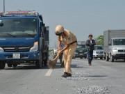Tin tức trong ngày - Cảnh sát giao thông đội nắng dọn đá rơi trên đại lộ