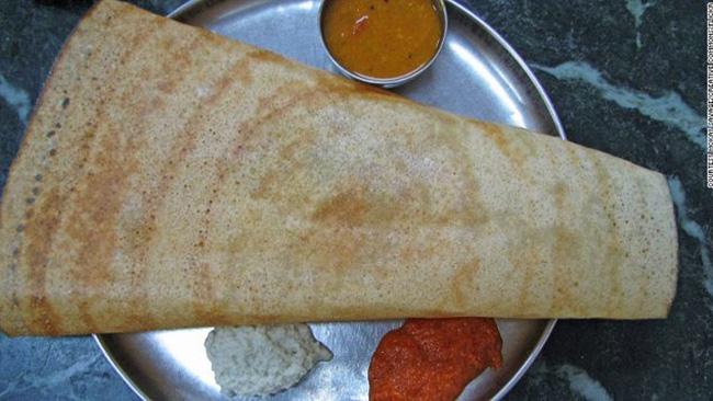 49. Masala dosa - Ấn Độ:  Một chiếc bánh bột gạo giòn tan, cuộn bên trong là khoai tây nghiền trộn sốt cay, sau đó chấm với nước sốt nấu từ cốt dừa, dưa muối, cà chua và đậu lăng cùng nhiều gia vị khác. Đây là món ăn sáng tuyệt vời, không chỉ ngon miệng mà còn giúp bạn no đến trưa.